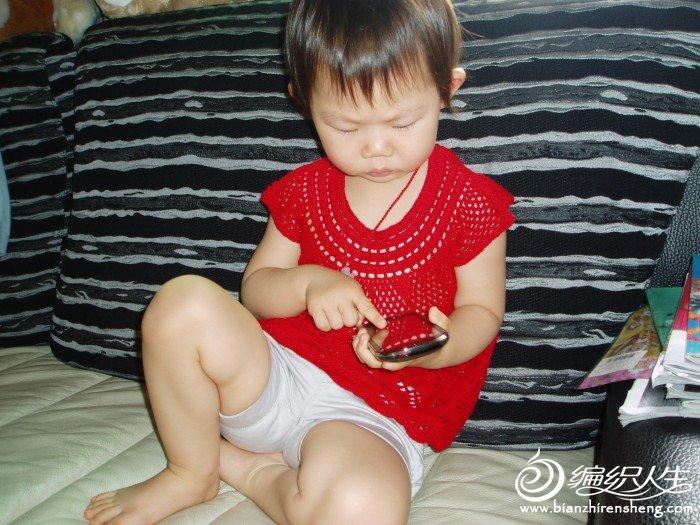 坐在沙发上玩爸爸的手机,瞧那认真劲