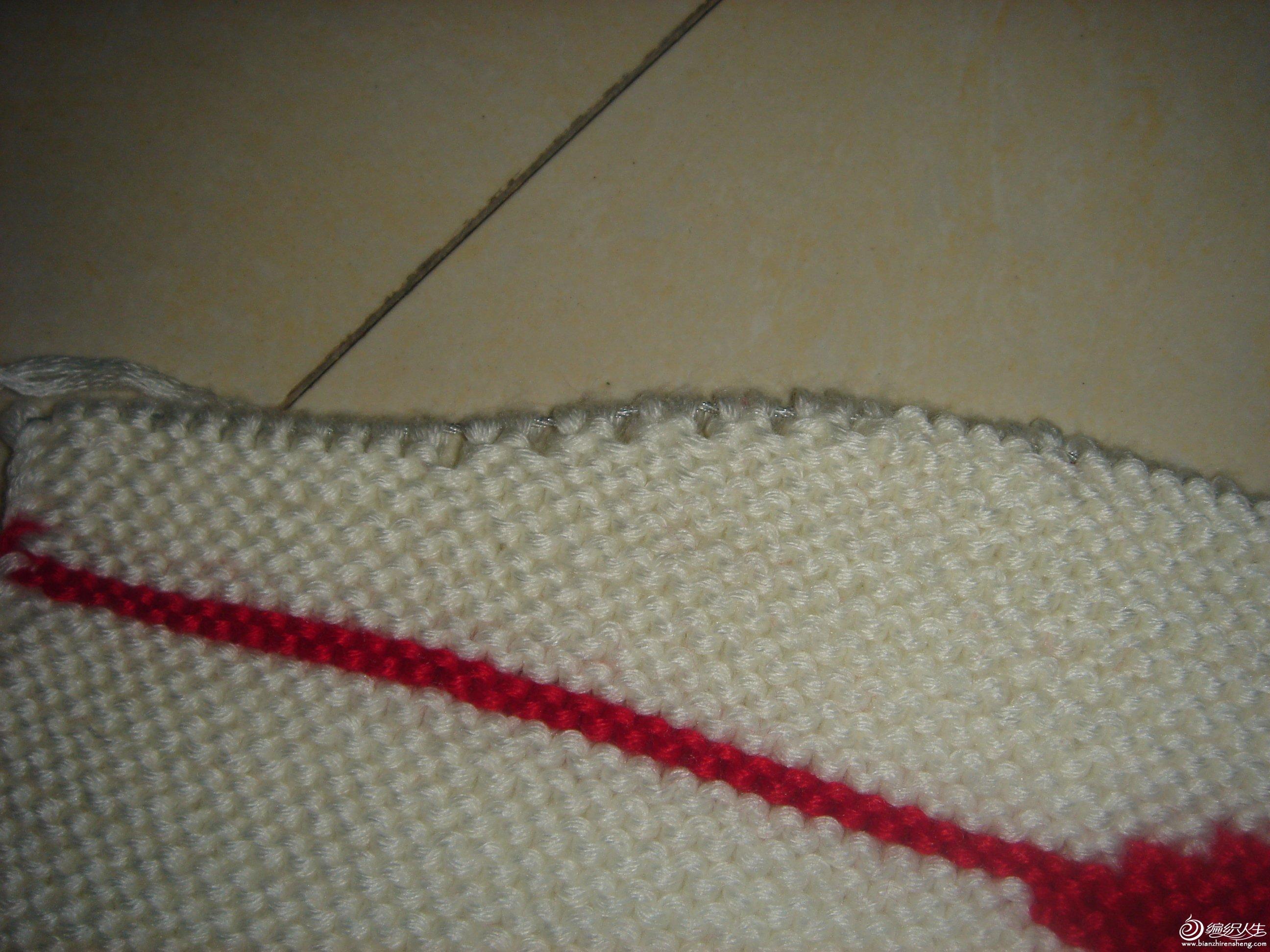 白线搓板针织11个来回,再用红线依次往前推,还是织11个来回的搓板针换红线只一个来回,再重新织花