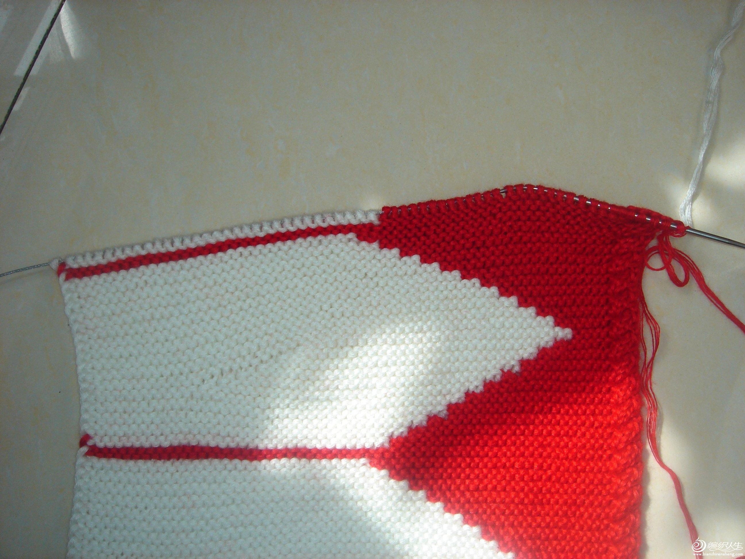 红线起60针边1针挑上4针拧麻花织搓板针5个来回,红线织30针换白线在织30针