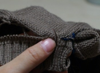 将衣服边包入机器领的缝隙中,从下穿入领子一侧的线圈将衣身和领缝合在一起,这里只缝合领的一侧