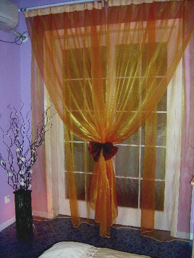 自己设计制作的窗帘。用料10M。是橘黄色的转色纱料,上面定制了白色的罗马杆,是专为兰花色的地板配置的,