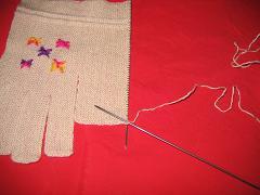 织大指进,在指顶的上面形成一条小辫子,我们从靠手套正面的那半边小辫子针上,每隔一个辫子孔,在第三个辫 ...